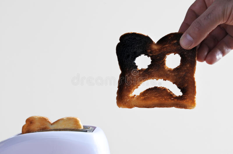 Hand holds one slices of burnt toast royalty free stock images