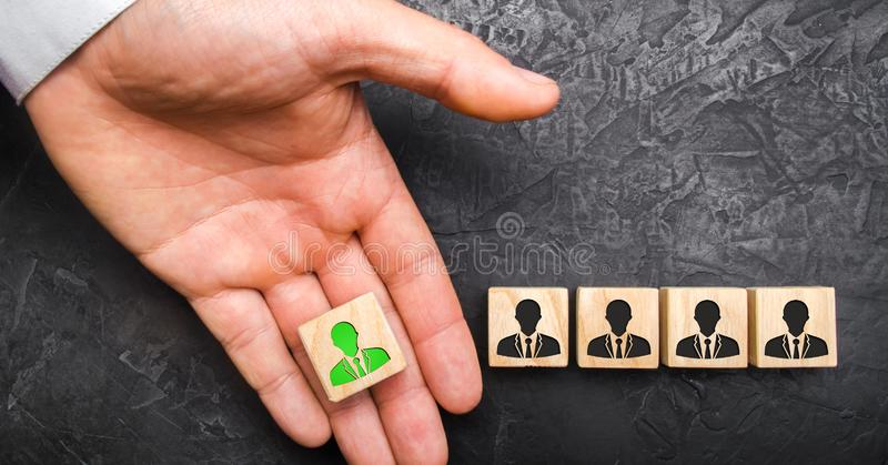 A hand holds out a green leader figure to a team of employees. Headhunter recruits staff and business personnel management. The concept of finding Specialists royalty free stock photography