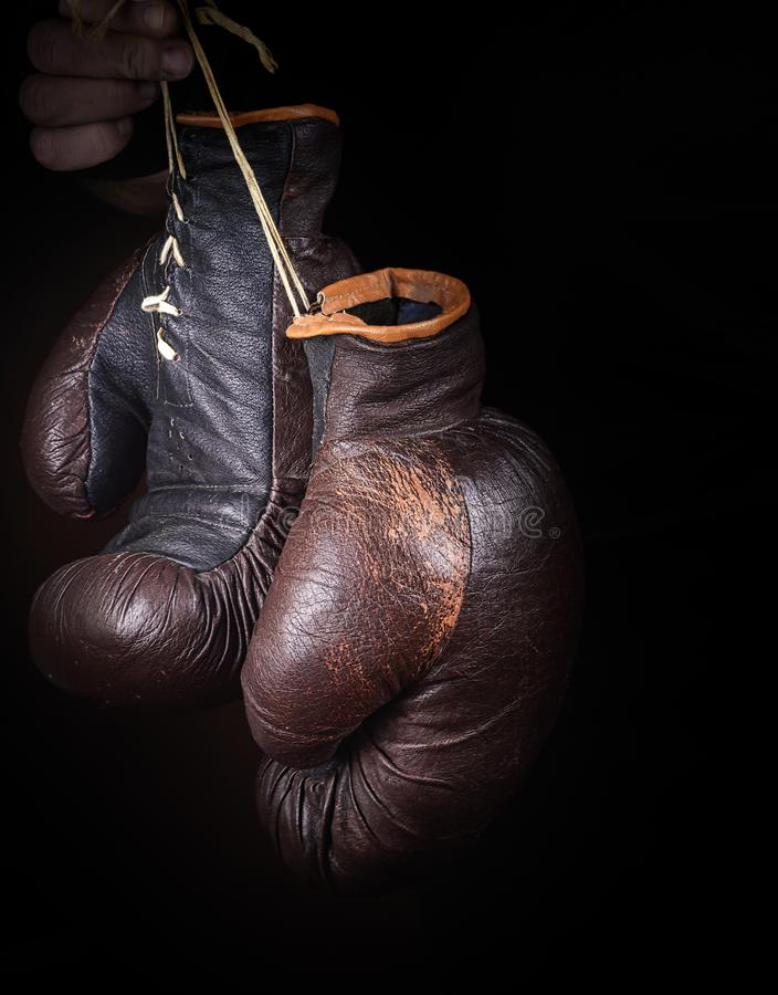 Hand holds a pair of brown very old boxing gloves. On a string, black background royalty free stock photos