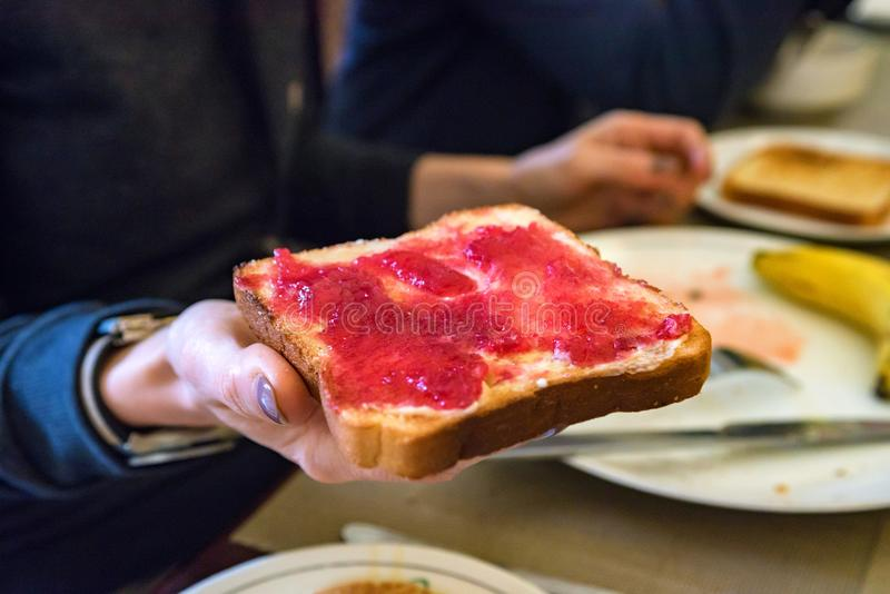 Hand holds a piece of bread with red jam stock photography