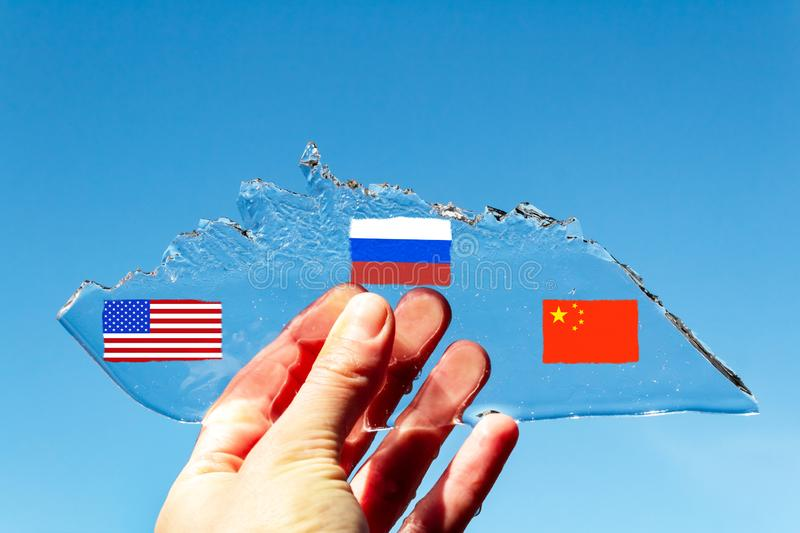 Hand holds a piece of ice in the shape of an Arctic iceberg against a blue clear sky, on which are drawn the flags of the states. A hand holds a piece of ice in stock images