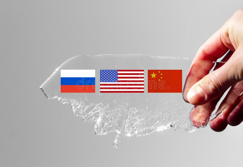 Hand holds a piece of ice in the shape of an Arctic iceberg against a blue clear sky, on which are drawn the flags of the states. A hand holds a piece of ice in royalty free stock images