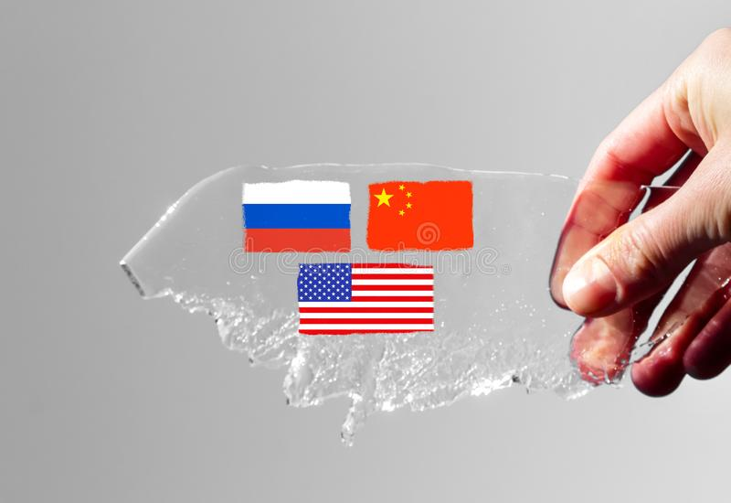Hand holds a piece of ice in the shape of an Arctic iceberg on a gray background, on which are drawn the flags of the states of. A hand holds a piece of ice in stock photo