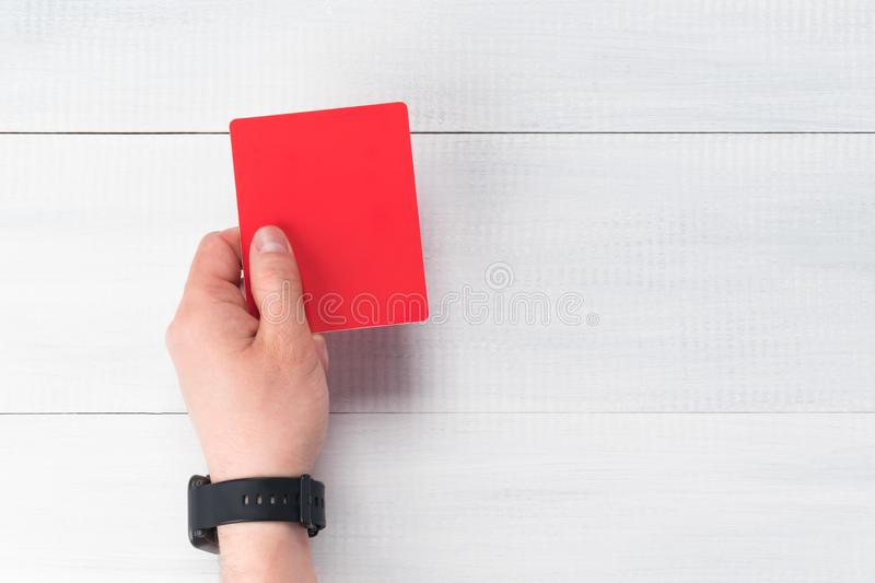 Hand holds a red card for violation on a football match, close-up royalty free stock image