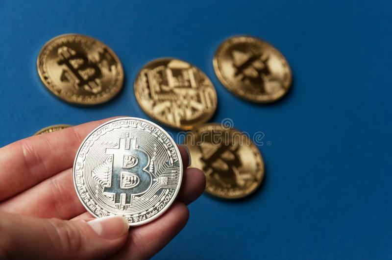 The hand holds a silver coin bitcoin on a blue background. The concept of crypto currencies royalty free stock photo
