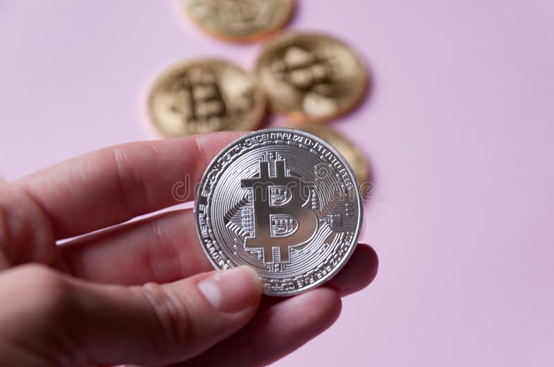 The hand holds a silver coin bitcoin on a pinkbackground. In the background there are several gold coins bitcoin. stock photo