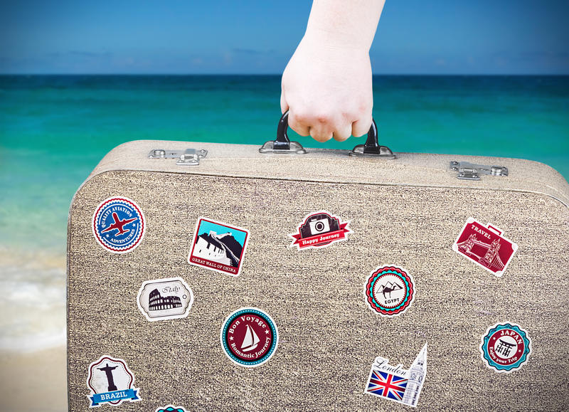 Hand holds a suitcase with stickers royalty free stock photos