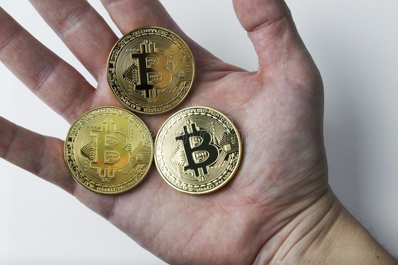 The hand holds three bitcoin on a white background. stock photo
