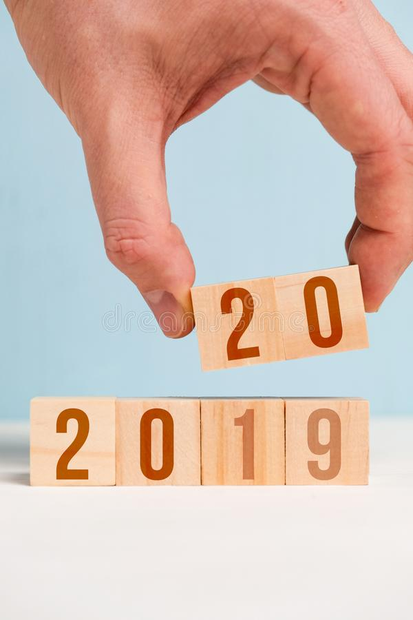 The hand holds two dice with numbers 20. The concept of changing the year from 2019 to 2020. Closeu p royalty free stock photography
