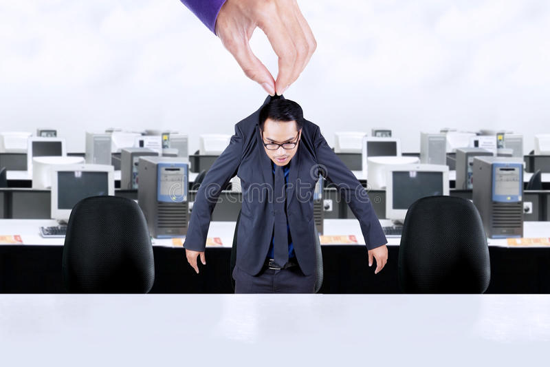 Hand holds worker in the office. Picture of hand holding a businessman in the office and put him on the office chair stock photos
