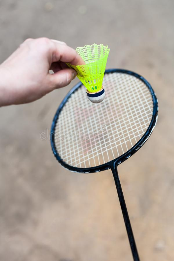 Yellow shuttlecock over badminton racquet stock photos