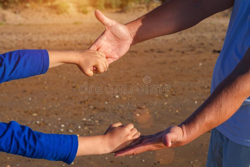 Hand in hand houdt de papa het close-up van de zoons` s hand stock foto's