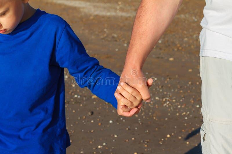 Hand in hand houdt de papa het close-up van de zoons` s hand stock fotografie