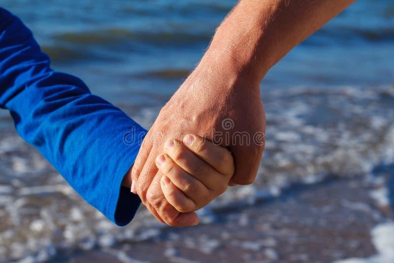 Hand in hand houdt de papa het close-up van de zoons` s hand stock afbeelding