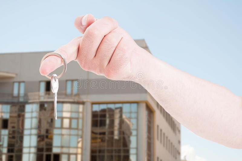 Hand with a house key in closeup. Hand with a house key on index finger in closeup as real estate or rental concept royalty free stock photography