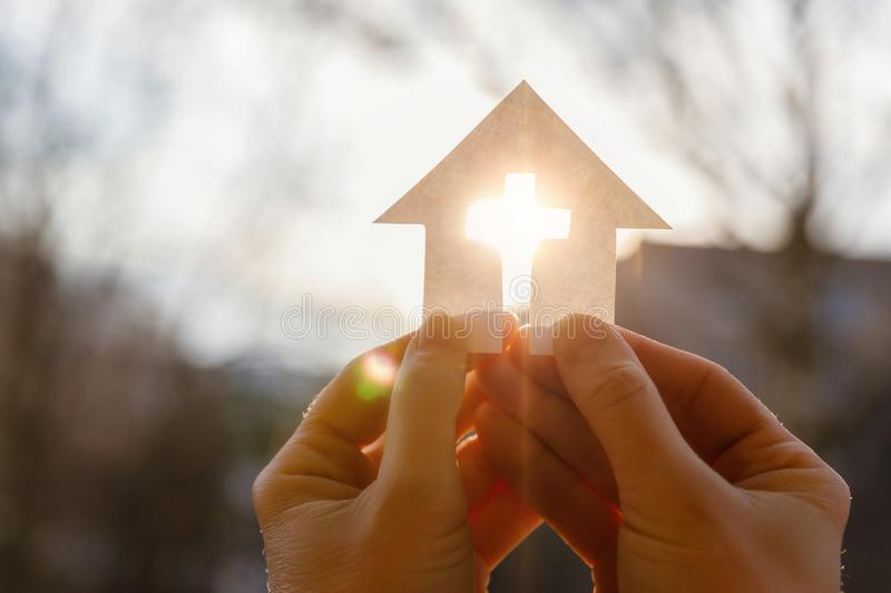 Hand with a house from paper and a cross. stock photography