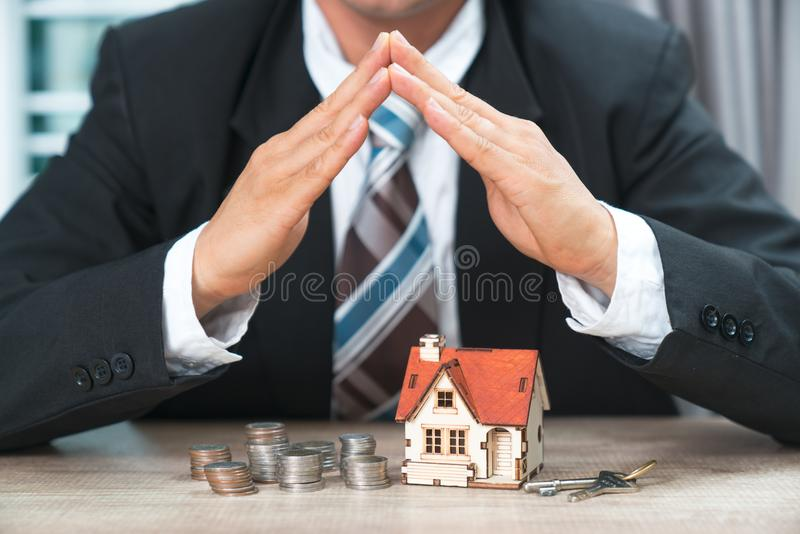 Hand hovering small family house, home insurance concept.  royalty free stock photos