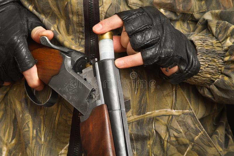 Hand of the hunter puts a cartridge in a shotgun stock photos