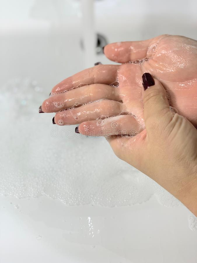 Hand hygiene.Spraying clean water from a faucet. Hand hygiene. Spraying clean water from a faucet. Skin hygiene, fighting microbes. White ceramic sink in a stock photos