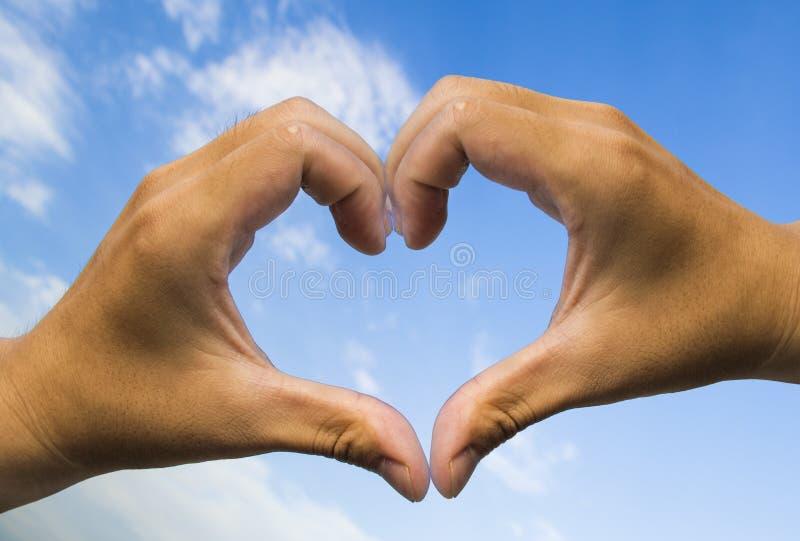 Hand i blå himmel för hjärtaformförälskelse royaltyfri fotografi