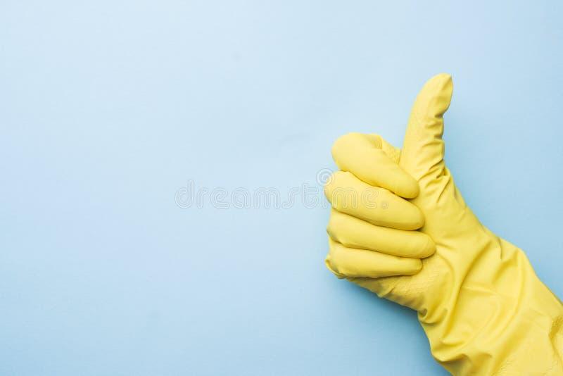 Hand i gula handskar för att göra ren på blå bakgrund tum upp Hem- lokalv?rdbegrepp royaltyfria bilder