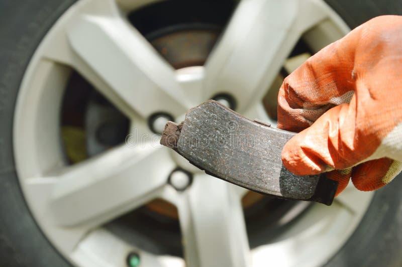 Hand i handsken som rymmer ogiltigt bromsfoder för ändrande på hjulbakgrund royaltyfri foto
