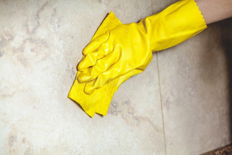 Hand i handskewipestegelplatta med trasan arkivfoton