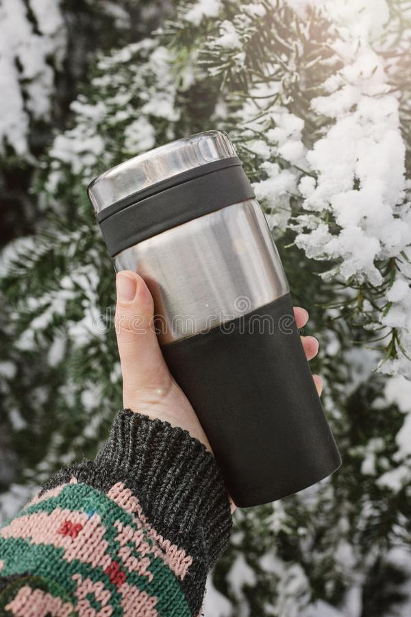 A hand i holding a Reusable Thermo mug, thermos, travel mug on the background of a snow-covered coniferous tree, winter outside. A hand in a warm sweater royalty free stock photos