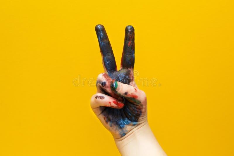Hand i mång--färgad målarfärg och att visa ett tecken av segern och frednärbilden som isoleras på en gul bakgrund arkivbilder
