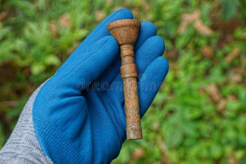 Hand im blauen Handschuh hält altes Bronzemundstück lizenzfreie stockfotografie
