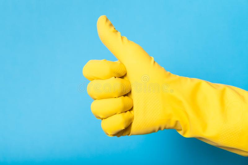 Hand im gelben Handschuh, Plastiklatex Daumen oben lizenzfreies stockbild