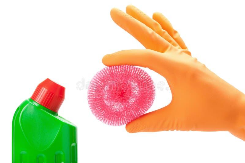 Hand im Gummihandschuh mit scheuern Auflage und Flaschen lizenzfreies stockfoto