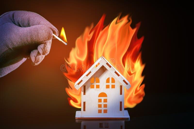 Hand im Handschuh mit einem brennenden Match legt Feuer auf das Hausmodell des Matches, Risiko, Immobiliarversicherung Haus und F lizenzfreie stockfotografie