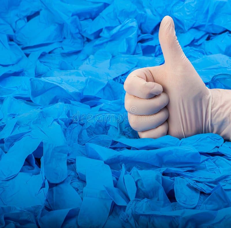 Hand im medizinischen Handschuh des neuen weißen Latex auf Hintergrund von viel blauen Gummihandschuhen lizenzfreies stockbild