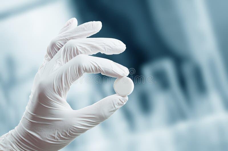 Hand im medizinischen Handschuh hält eine Tablette stockfotografie