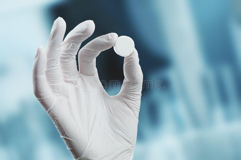 Hand im medizinischen Handschuh hält eine Tablette stockfoto