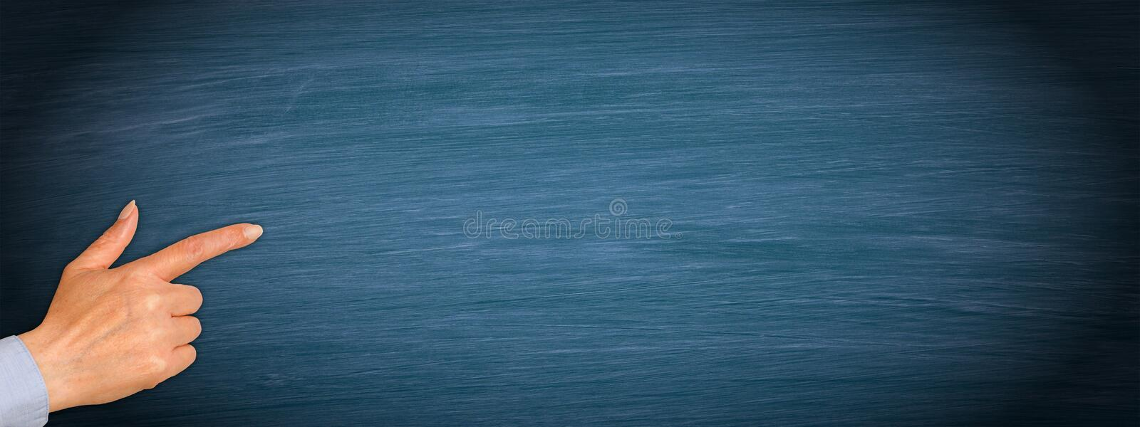 Hand with index finger on empty blue chalkboard background. Female hand with index finger on empty blue chalkboard background, copy space for individual text royalty free stock photo