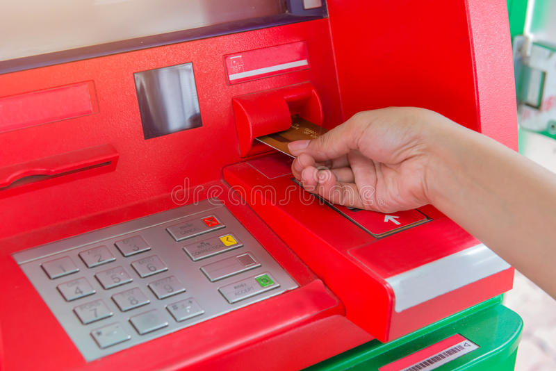 Hand insert credit card to ATM bank cash machine for withdraw mo royalty free stock photo