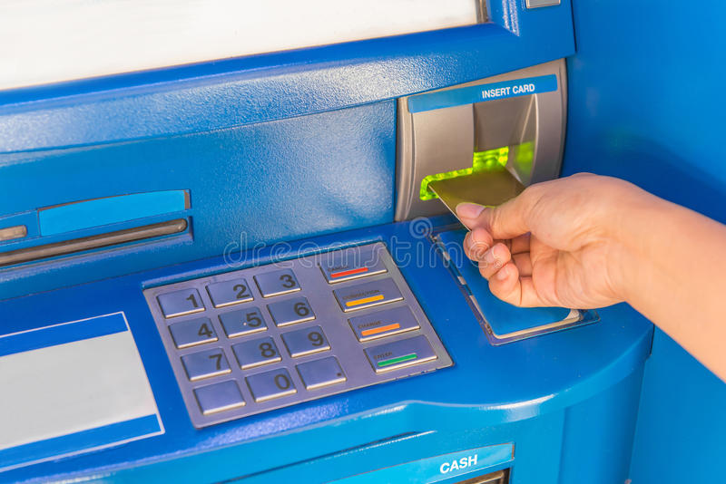 Hand insert credit card to ATM bank cash machine for withdraw mo. Ney royalty free stock images