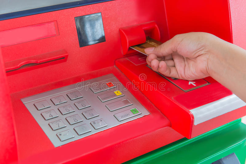Hand insert credit card to ATM bank cash machine for withdraw mo stock photo