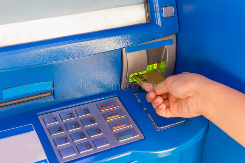 Hand insert credit card to ATM bank cash machine for withdraw mo. Ney stock photography