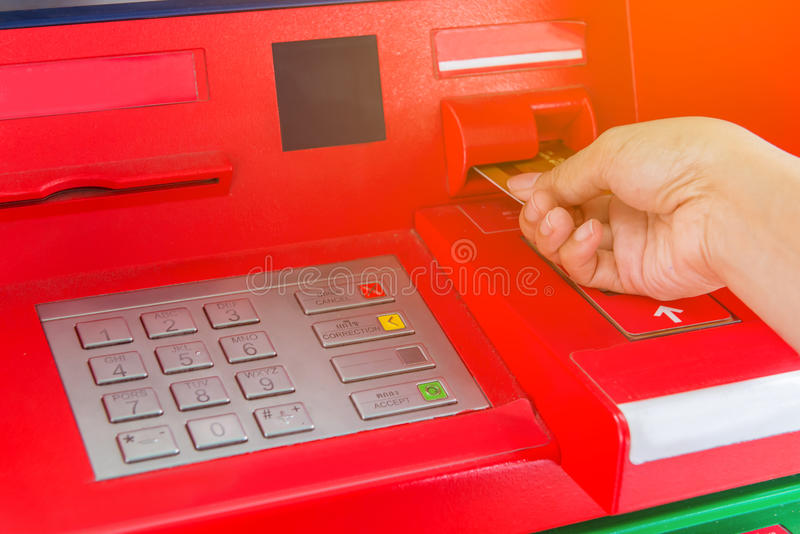 Hand insert credit card to ATM bank cash machine for withdraw mo stock image
