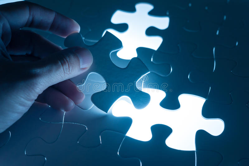 Hand insert jigsaw, conceptual image of business strategy, decision making concept stock image