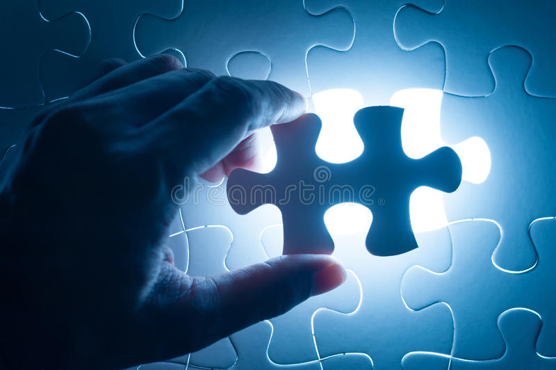Hand insert jigsaw, conceptual image of business strategy. Decision making concept stock photos