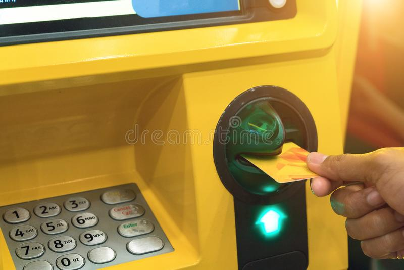 Hand inserting ATM card into bank machine to withdraw money royalty free stock photo