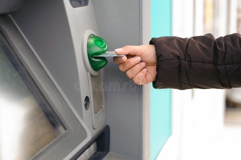 Hand inserting ATM card into bank machine to withdraw money royalty free stock images