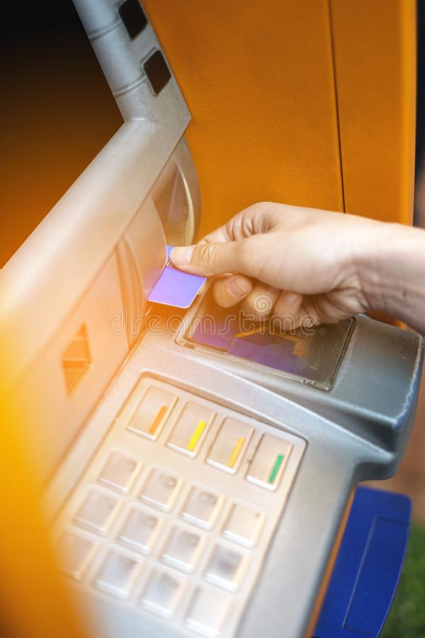 Hand inserting ATM card into ATM bank machine for withdrawing money. royalty free stock photography
