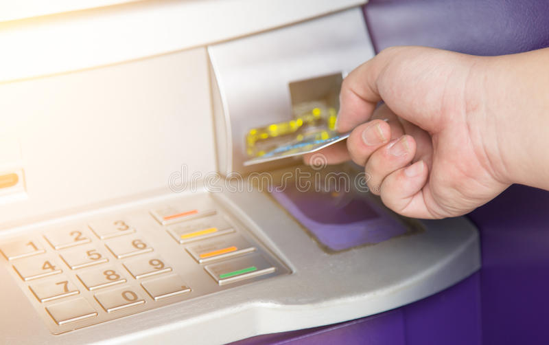 Hand inserting ATM credit card into bank machine. With light royalty free stock photo