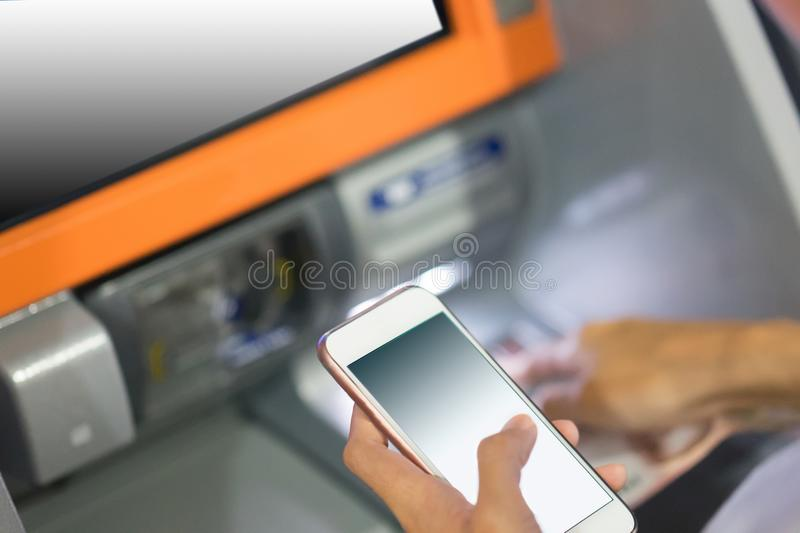 Hand inserting a credit card in an atm holding smart phone stock images