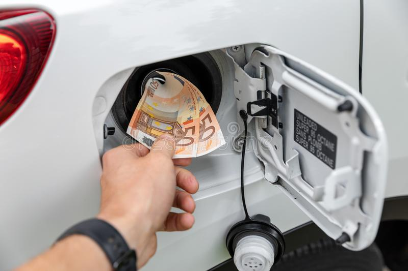 Hand inserting money in car fuel tank stock photo